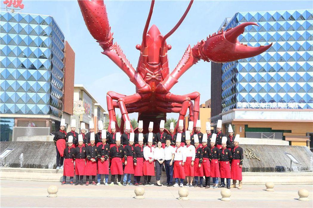 潛江龍蝦學院師生在龍蝦雕塑前合影。 圖/取材自微信