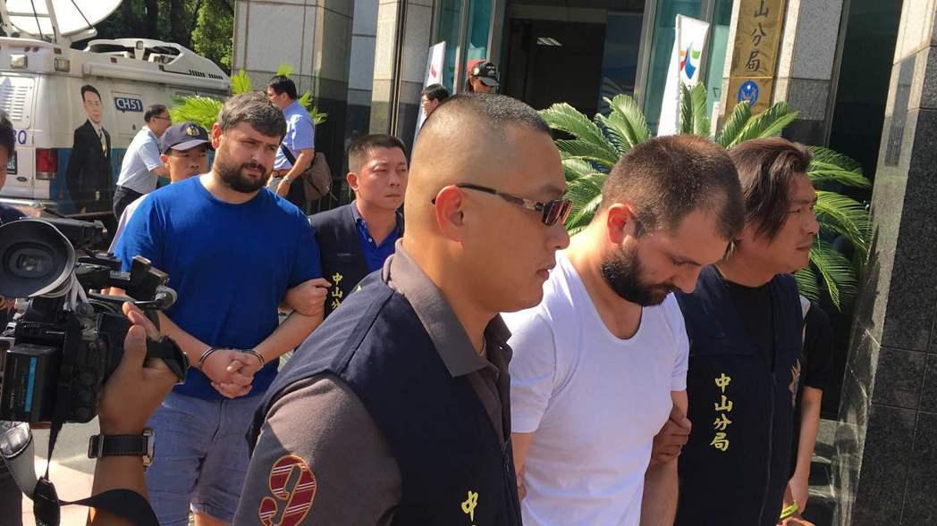 警方提訊一銀盜領案嫌犯米海爾(藍衣者)和潘可夫(白衣者)。 圖/本報系資料照片