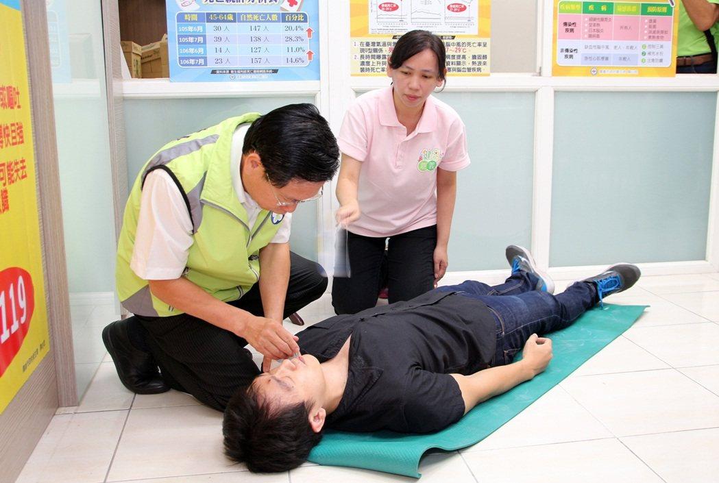 嘉義市長涂醒哲(左)今天親自示範如何幫助中暑者。記者姜宜菁/攝影