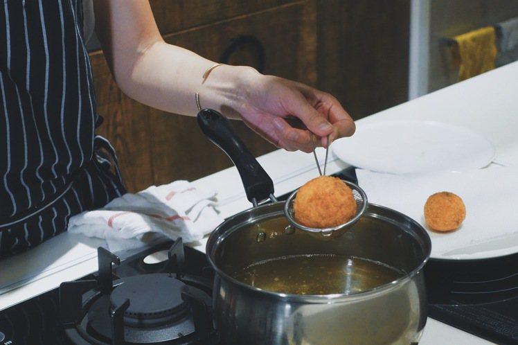 Yen專心炸製西西里炸飯糰。圖/PJ攝影