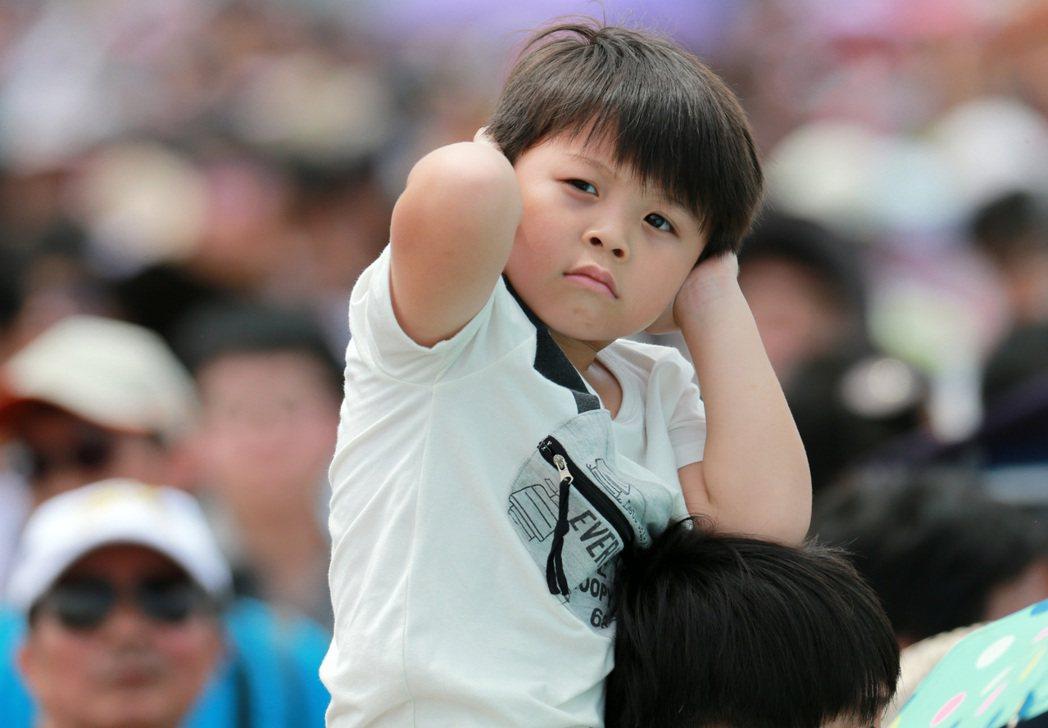 由於現場戰機表演聲響過大,一名位小朋友忍不住嗚住雙耳。記者劉學聖/攝影