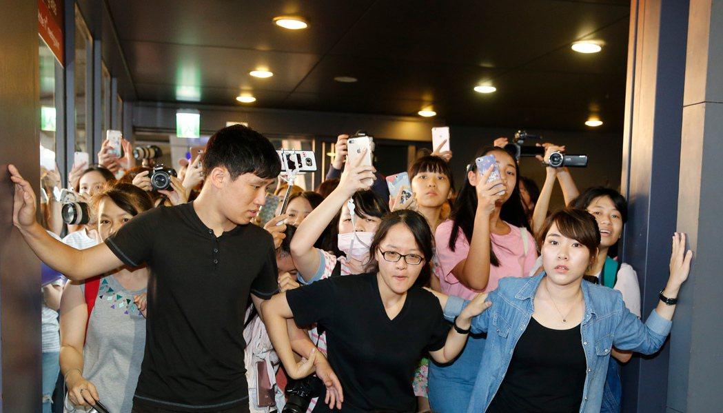 韓團VIXX傍晚抵台,近兩百位粉絲到機場接機,工作人員在門口擋住熱情的粉絲。記者...