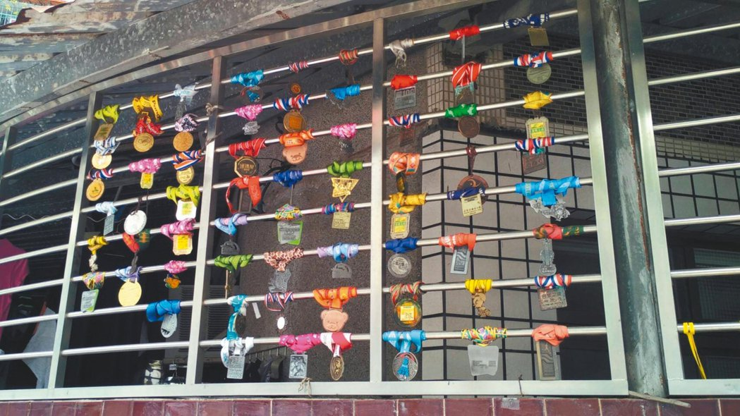 每每看著這座屋子鐵欄杆上吊掛著五彩繽紛的路跑獎牌,內心總是非常佩服,認為這位屋主...
