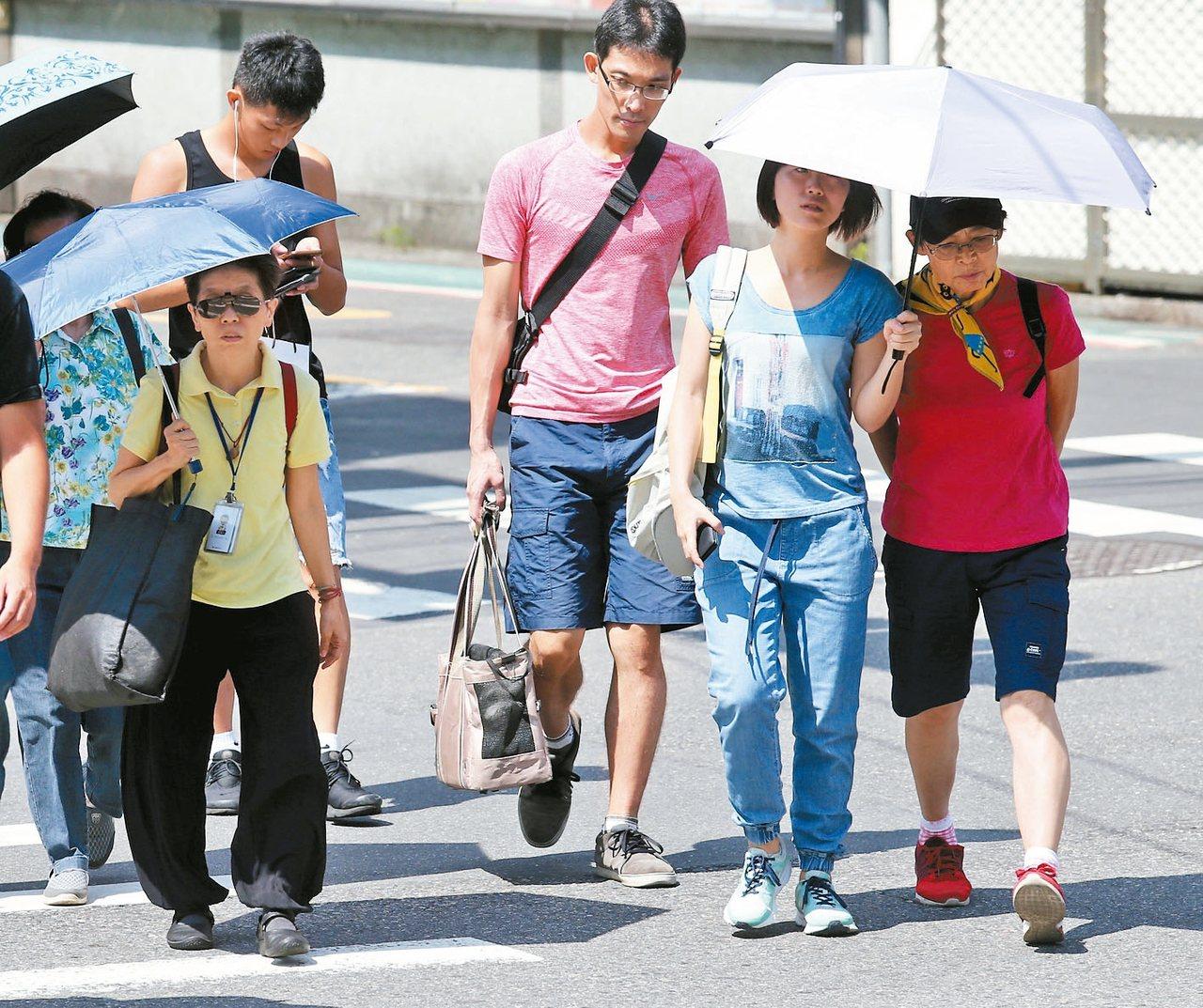 中央氣象局表示,今天全台各地大多是晴朗炎熱的天氣,各地高溫普遍在33到35度左右,其中大台北地區有可能出現37度的高溫,民眾撐傘抵擋毒辣的豔陽。 記者鄭清元/攝影