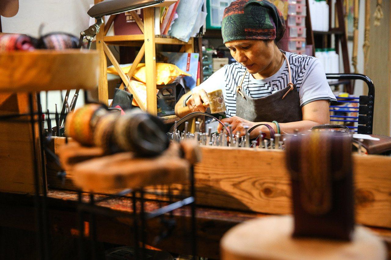 店長烏瑪專注地製作原住民風格的特色皮件。
