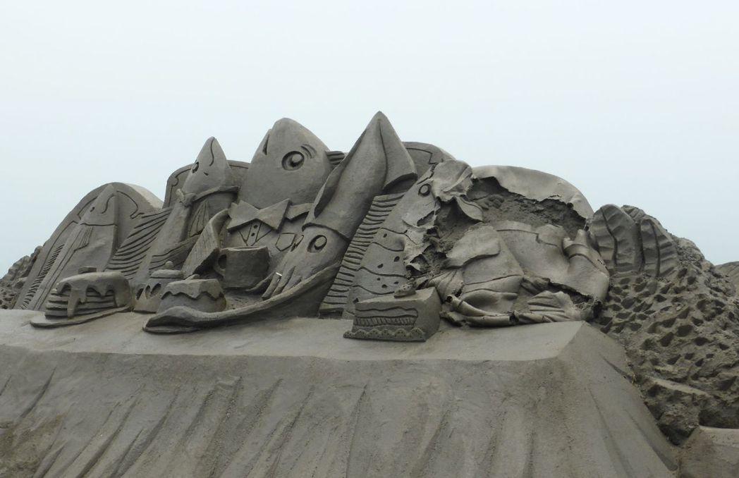 高雄旗津黑沙玩藝節的部分沙雕被大雨侵襲、烈日照射之後,表面垮落待修補。圖/聯合報...