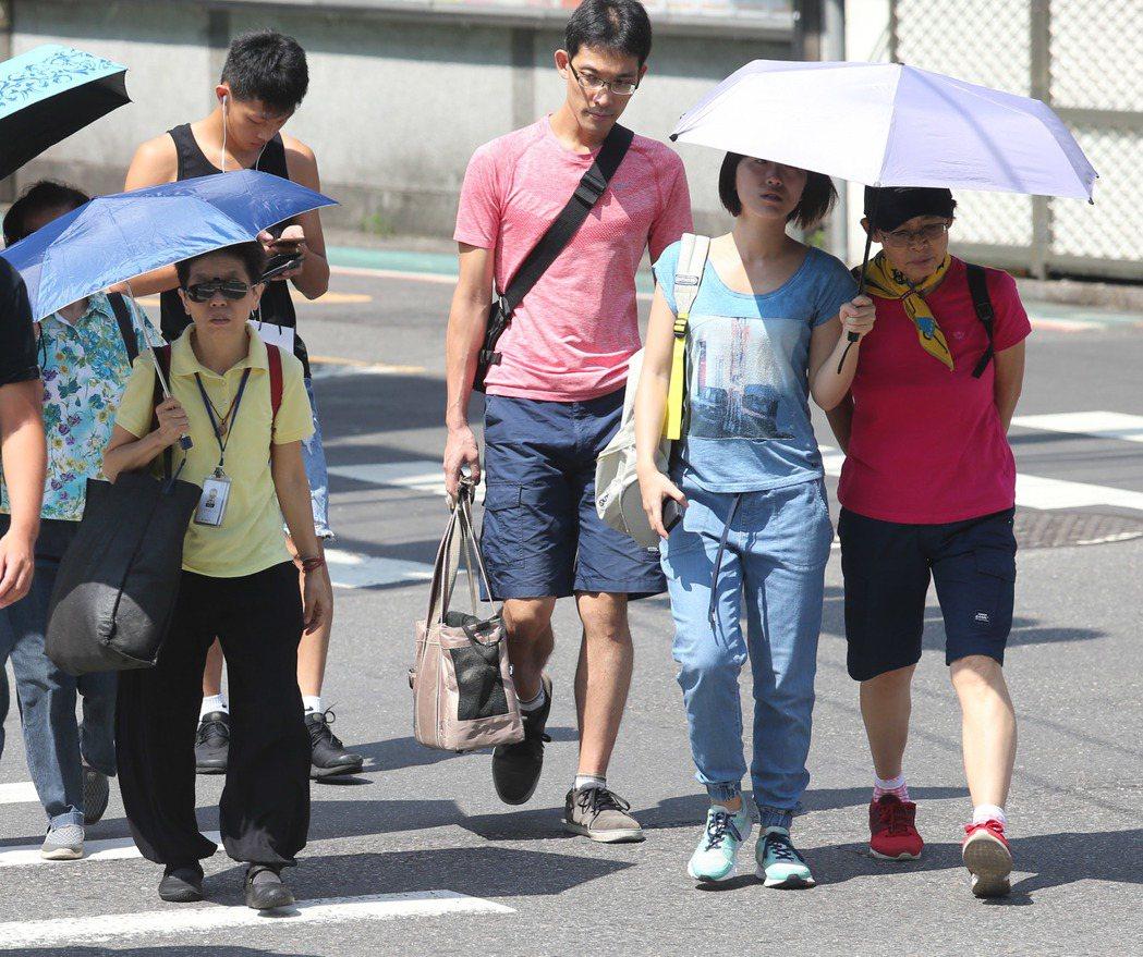 民眾撐傘防止劇烈日曬。記者鄭清元/攝影