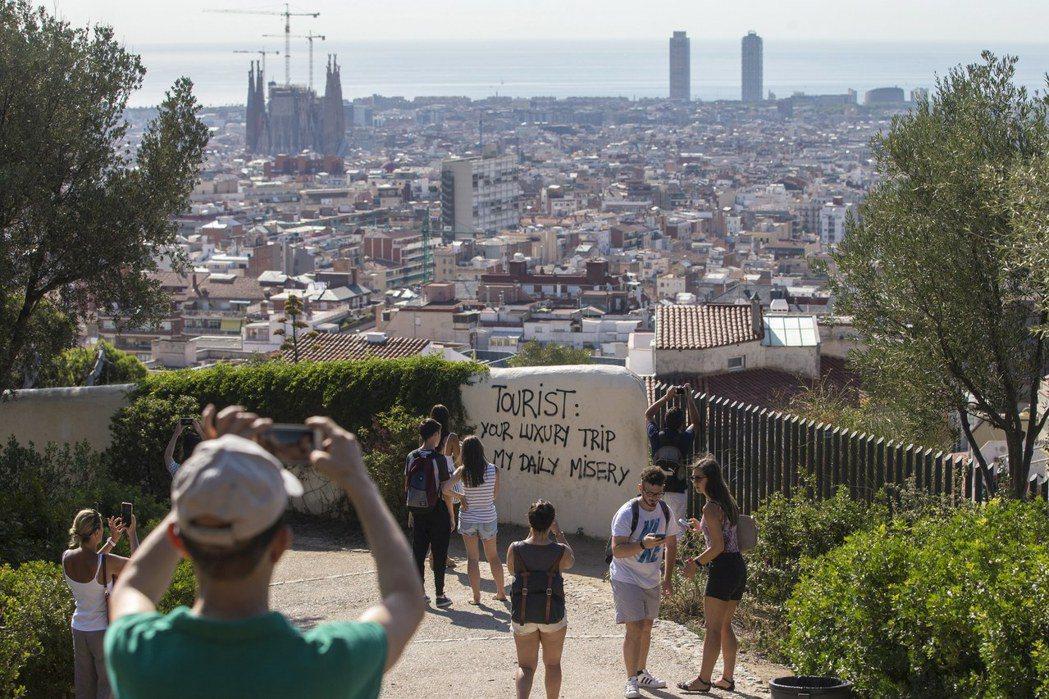 西班牙巴賽隆納居民不滿觀光客湧入降低生活品質,在市區牆面噴漆寫上「觀光客:你的奢...