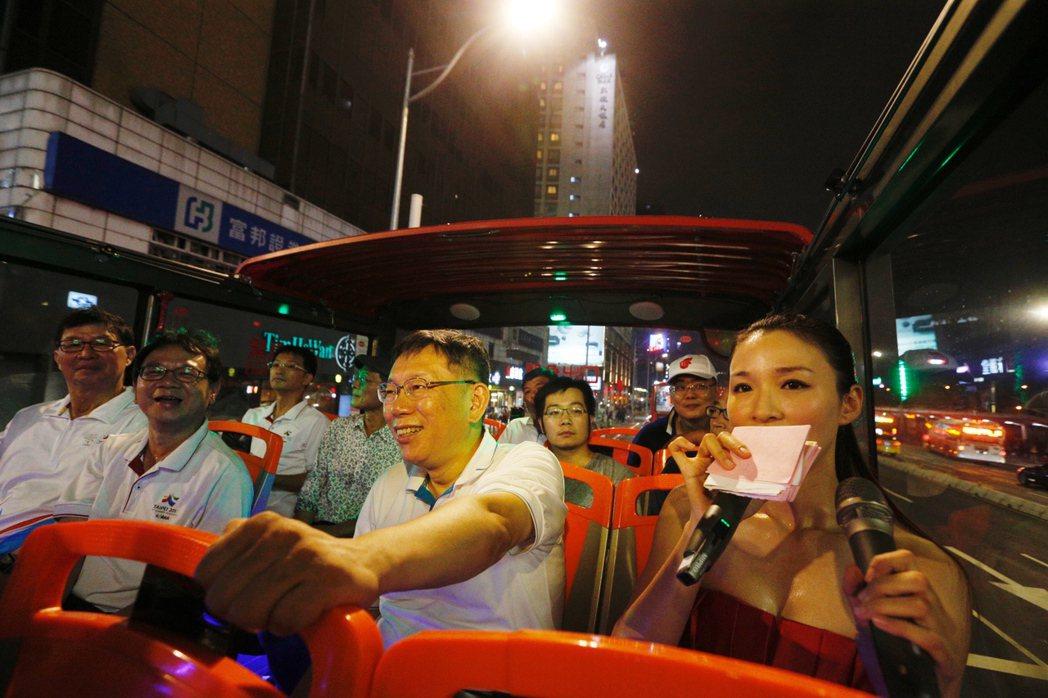 台北市長柯文哲(中)今晚主持「燦爛的台北城,燈峰造極」,坐上觀光巴士,繞行東門、...