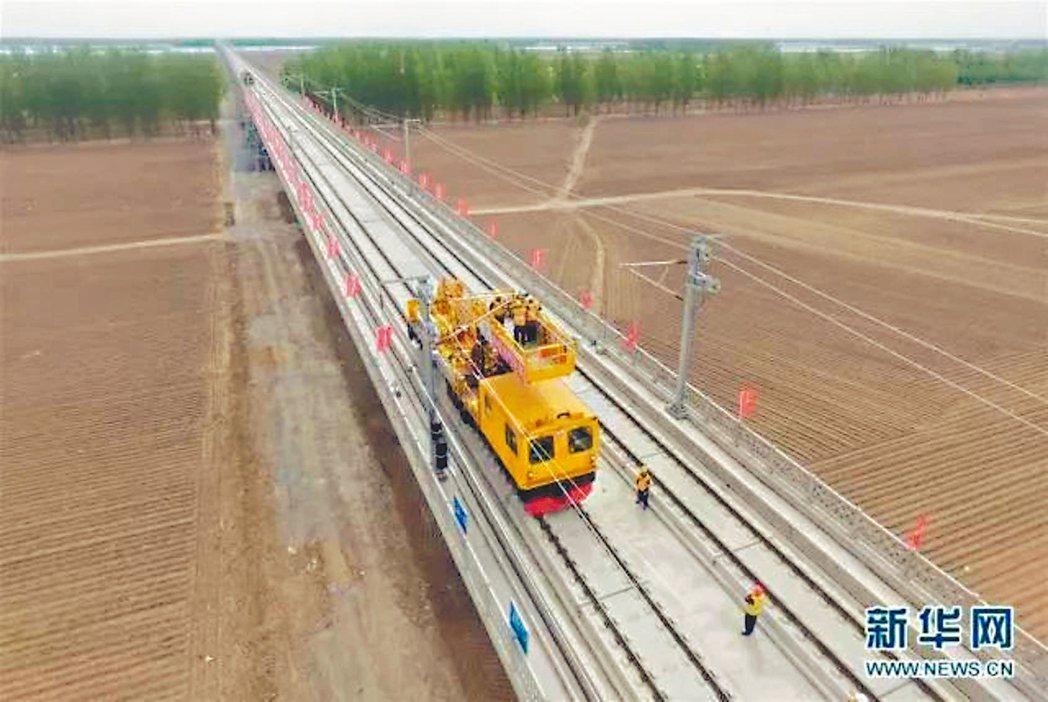 中鐵電氣化局施工人員進行接觸網架設施工作業。 (新華網)