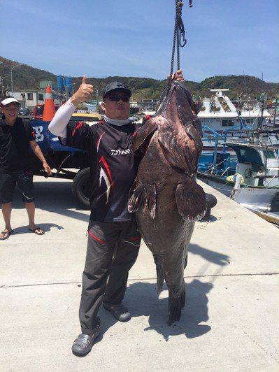 洪姓釣客在北方三島海域釣到1尾超大的七帶石斑,進港後開心合影。 記者曾健祐/翻攝