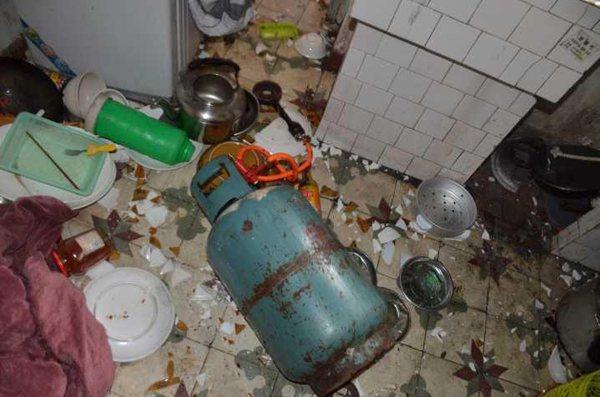 女子用瓦斯桶怒砸廚房。圖擷自澎湃新聞