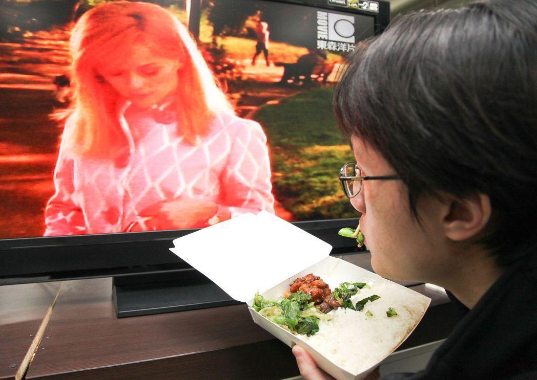 用餐時間,不少人喜歡一邊吃飯、一邊看電視消磨時間。 報系資料照