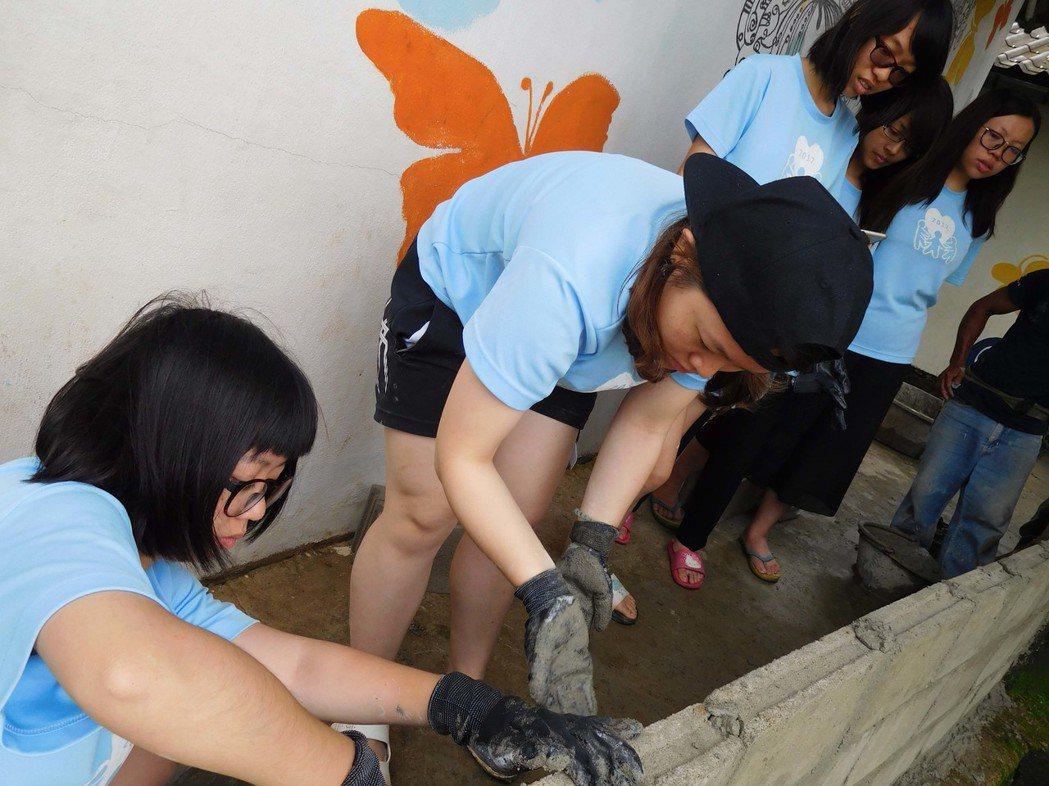 台科大學生到泰北偏鄉雲華小學服務,協助整修圍牆、教室地板。圖/台科大提供
