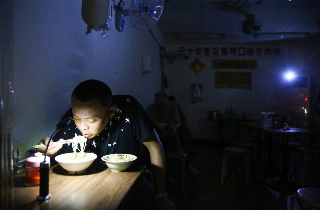 15日全台各地大跳電,民生社區許多小吃店在用餐時間受影響,只能摸黑用手電筒照明做...