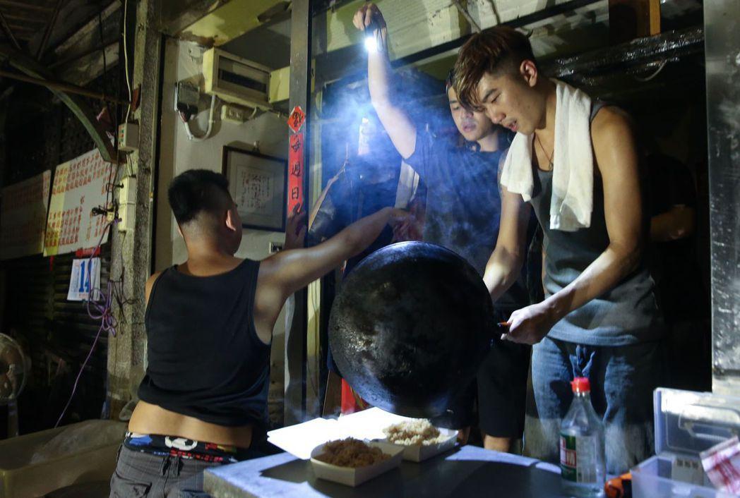 台北市民生社區昨晚許多小吃攤在用餐時間受停電影響,只能摸黑用手電筒照明繼續做生意...