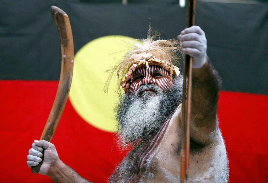 圖中原民長者背後為澳洲原住民旗幟:黑色代表原住民、紅色代表土地、中間黃色為太陽。...