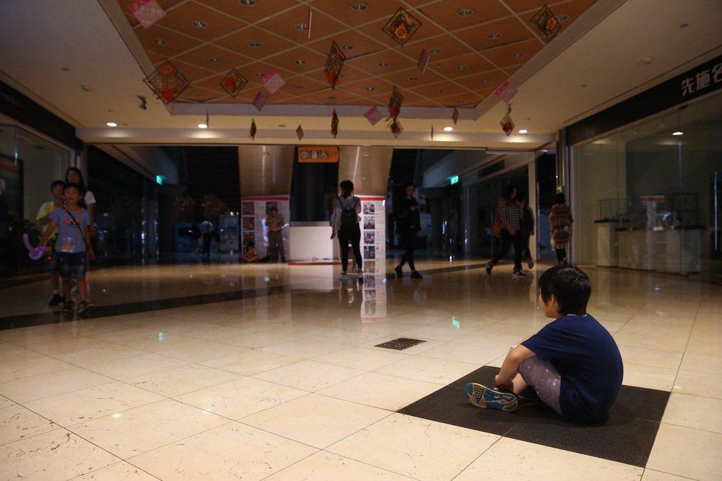 台北市京華城受停電影響,緊急啟動備用電力,一名小朋友坐在地上顯得無奈。 本報資料...