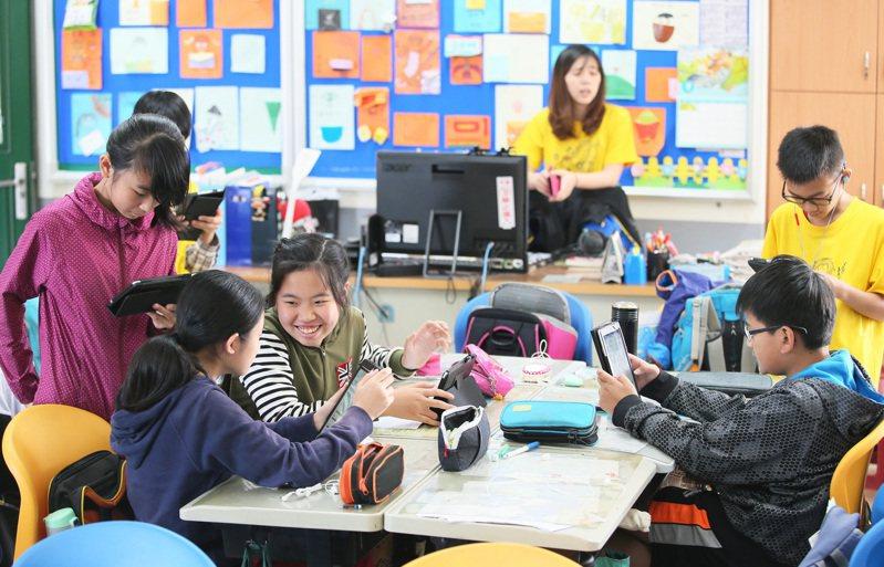三峽龍埔國小老師張芳婷透過多個數位學習平台融入教學,增強孩子的學習動機,許多學生在下課時仍拿著平板玩遊戲答題,準備參加學校的英檢電競比賽。本報資料照/記者潘俊宏攝影