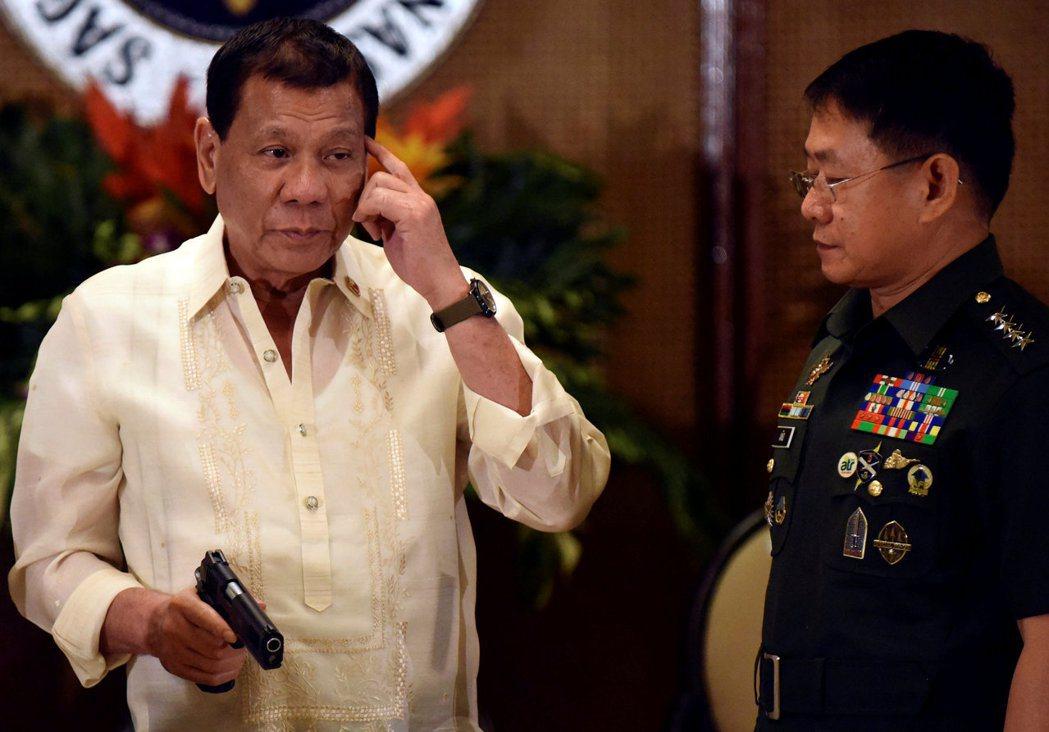 菲律賓總統杜特蒂在一場交接典禮上,拿著45口徑手槍。 (路透)