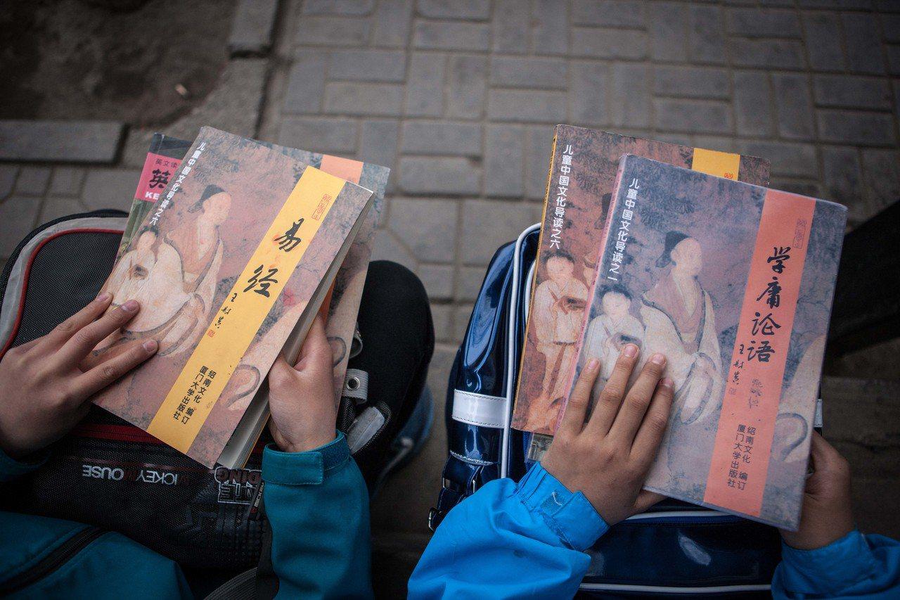 在寧夏回族自治區銀川市的一個公車站,在候車間隙分別誦讀《易經》和《學庸論語》。圖...