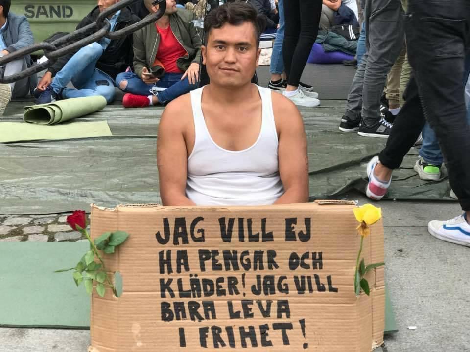 一名男子面對鏡頭微笑著,身前的紙板寫著:「我不要衣服也不要錢。我只想活在自由世界...