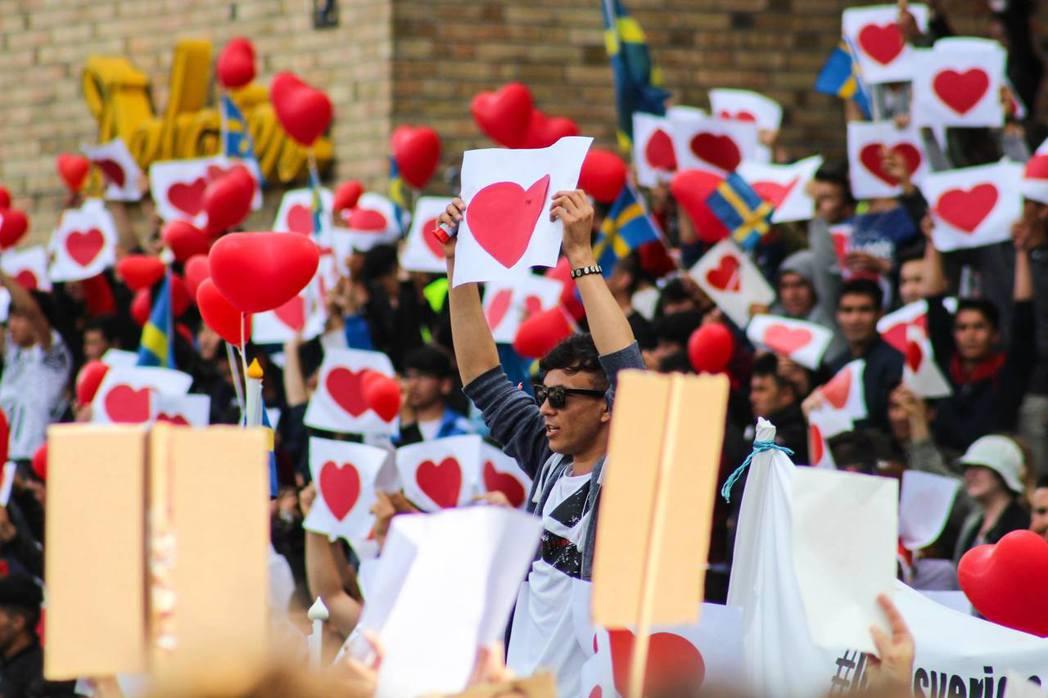 面對極右派的持續叫囂,群眾手持愛心圖案與瑞典國旗,用愛與尊重回應各方惡意。 圖/...