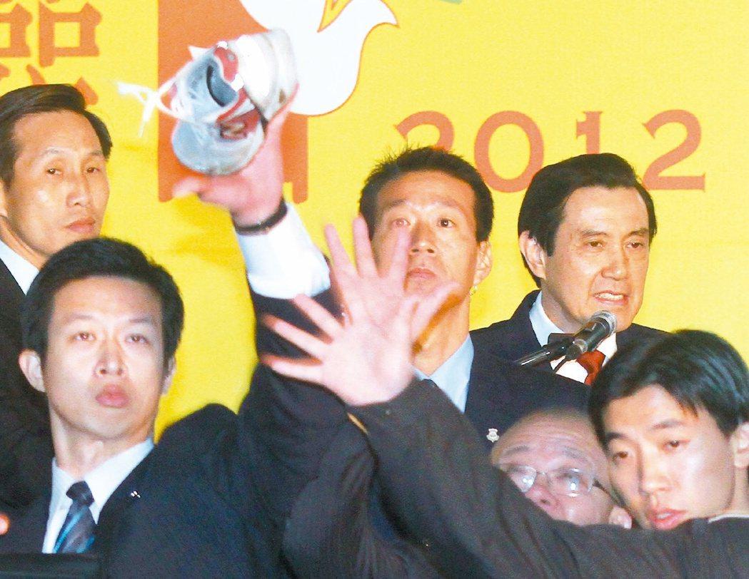 前總統馬英九(後右)2012年致詞時遭飛鞋攻擊,被已提高警覺的隨扈用手撥掉。 本...