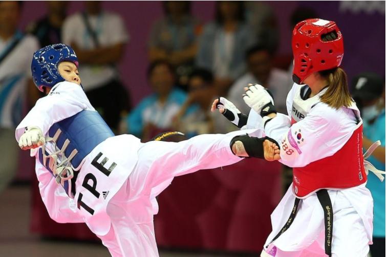 世大運跆拳道對打項目,我國選手莊佳佳(右)在女子67公斤級金牌戰敗給韓國對手,以...