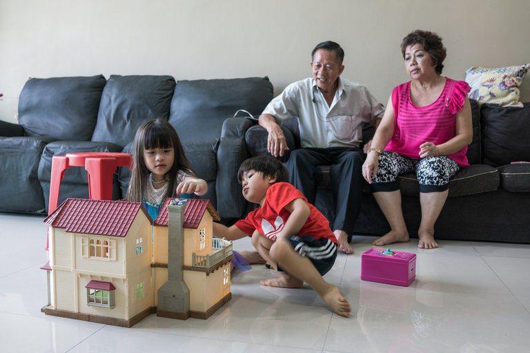 新加坡一對祖父母望著兩名孫子在客廳玩房子遊戲。 圖/取自紐約時報