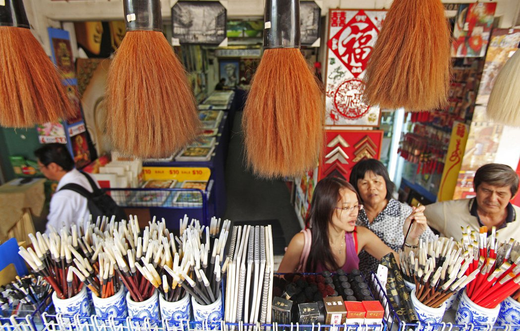 一名年輕新加坡人正在選購毛筆;許多年輕華人開始自力學習方言,期待能和只會說方言的...