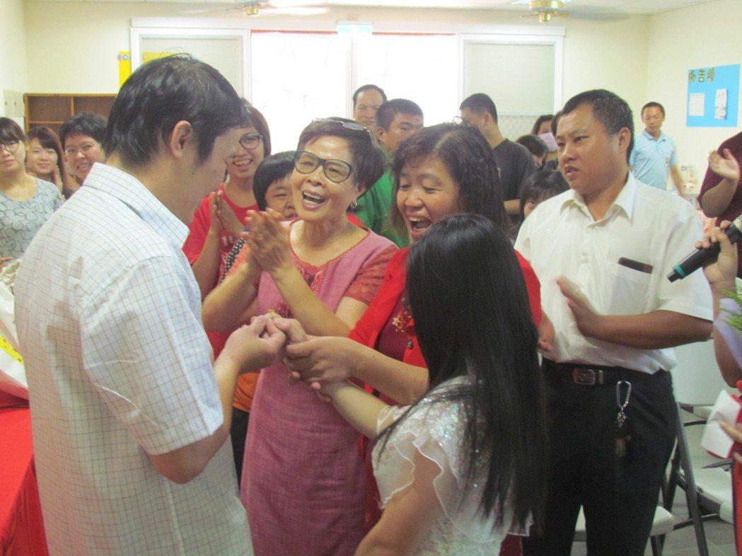 在眾人祝福下,「阿慶」(左)為「小雯」戴上訂婚戒指。記者張家樂/攝影