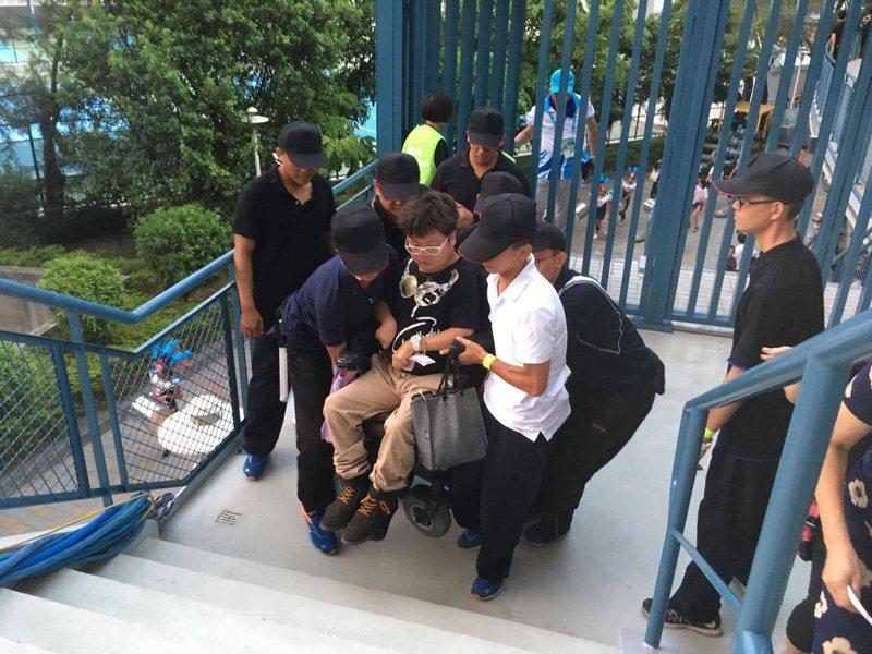 世大運開幕典禮現場,一位坐電動輪椅的年輕的身障男性周圍環饒著5-6名著黑衣黑帽的工作人員,他們以人力把這位身障者與他的輪椅抬扛上階梯。  圖/帥凱哥提供