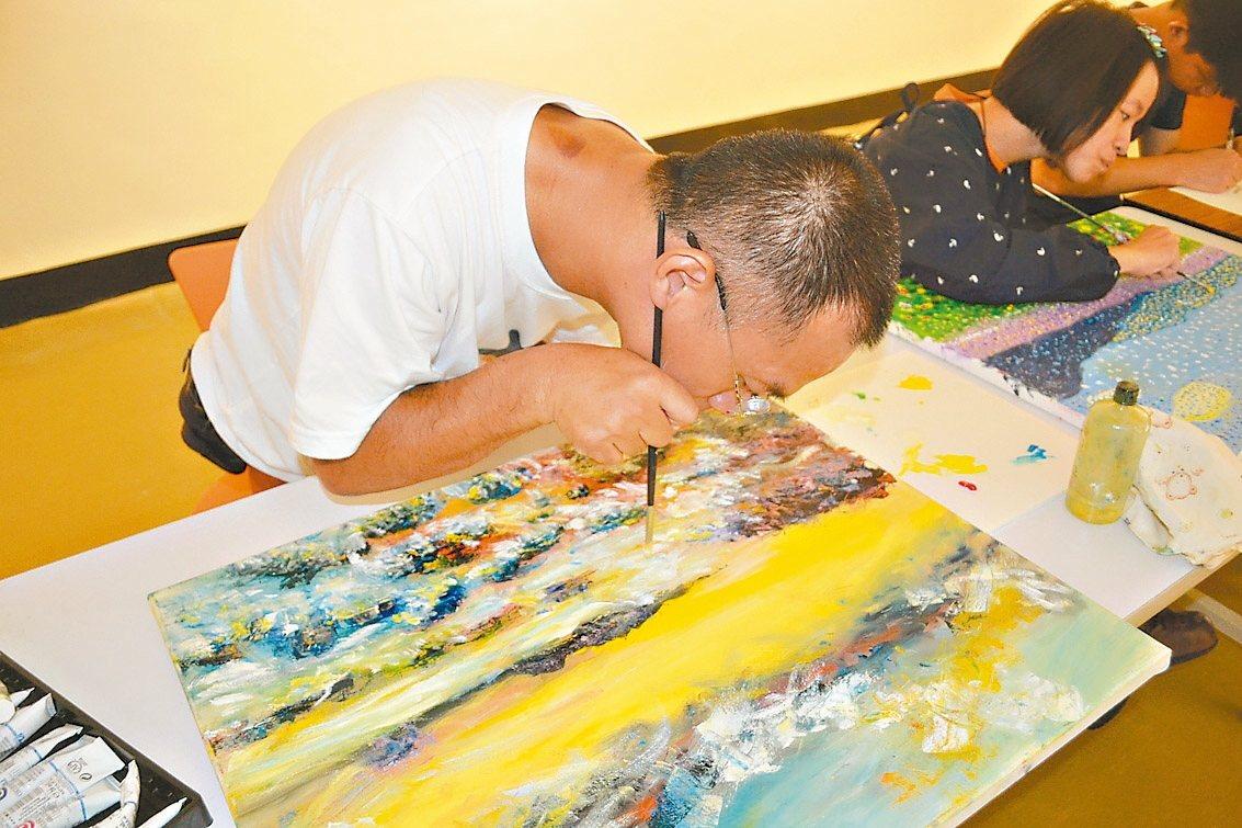 腦麻患者謝左華作畫時必須將畫筆貼近臉頰,才能畫出線條。 記者鄭惠仁/攝影