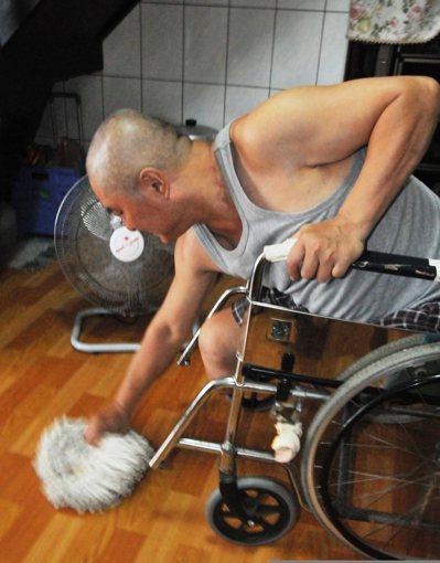 郭欽銘沒有雙腳,多年來一直用擦地板復健,一手抓坐椅,一手拿拖把頭擦地,家中地板總...