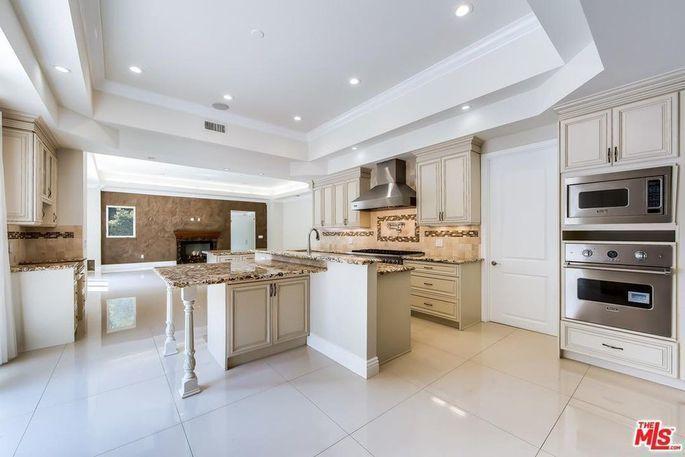 豪宅的廚房帶有不鏽鋼廚具、嵌入式的儲藏櫃、偌大的中島和訂製的櫥櫃。(Realto...