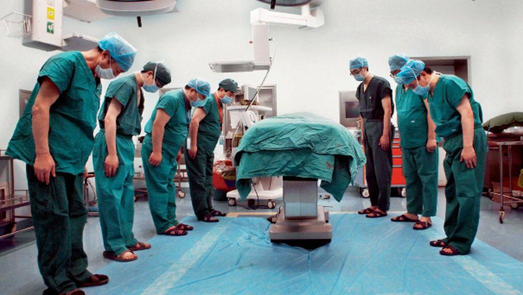 醫護人員向器官捐贈者遺體鞠躬感謝。 (澎湃新聞)
