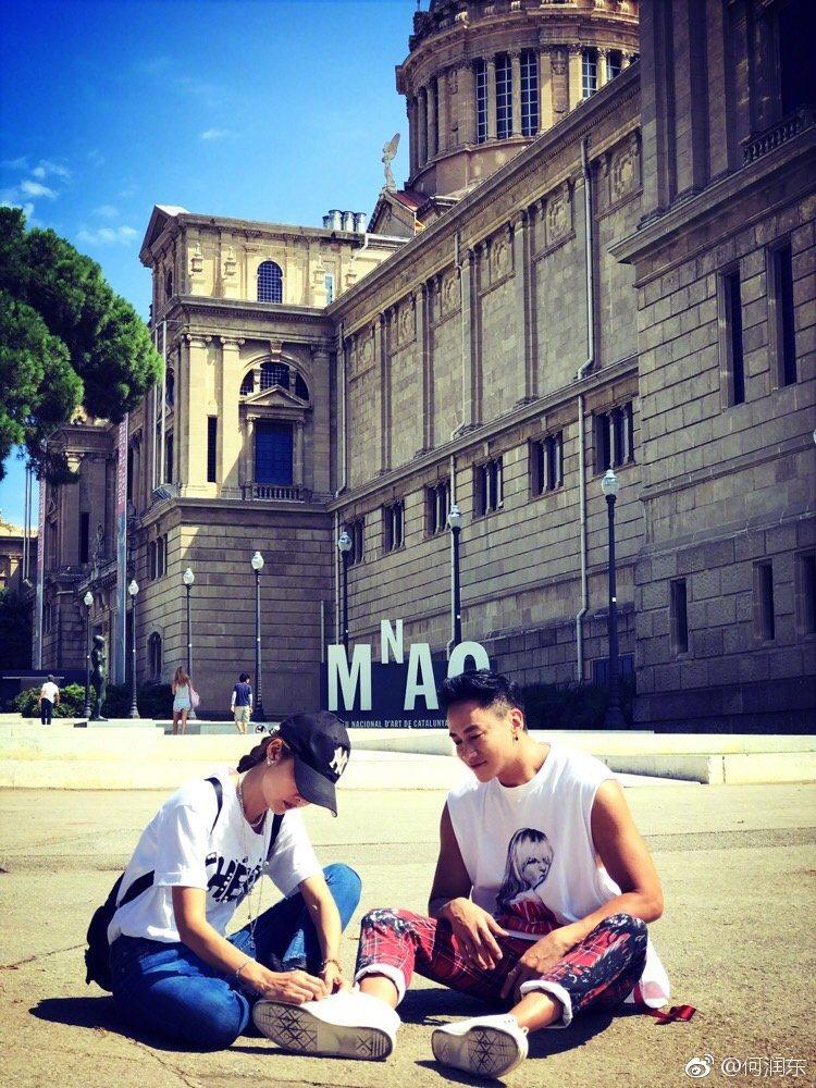 5日何潤東還曝光了與老婆在西班牙大街上的照片,只見老婆專心地幫他綁鞋帶,甜蜜爆表...