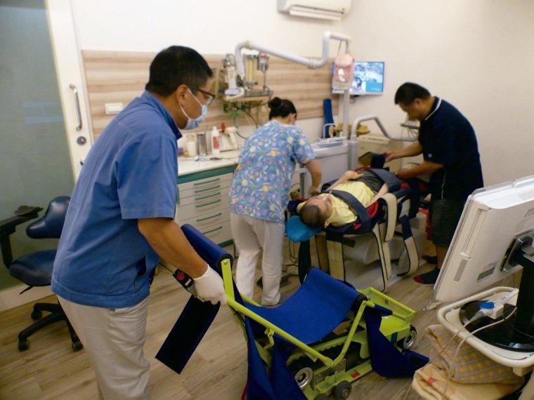 牙醫師羅界山(左)治療腦麻病患時,注意病患嗆咳問題,有水經口鼻都要很小心。