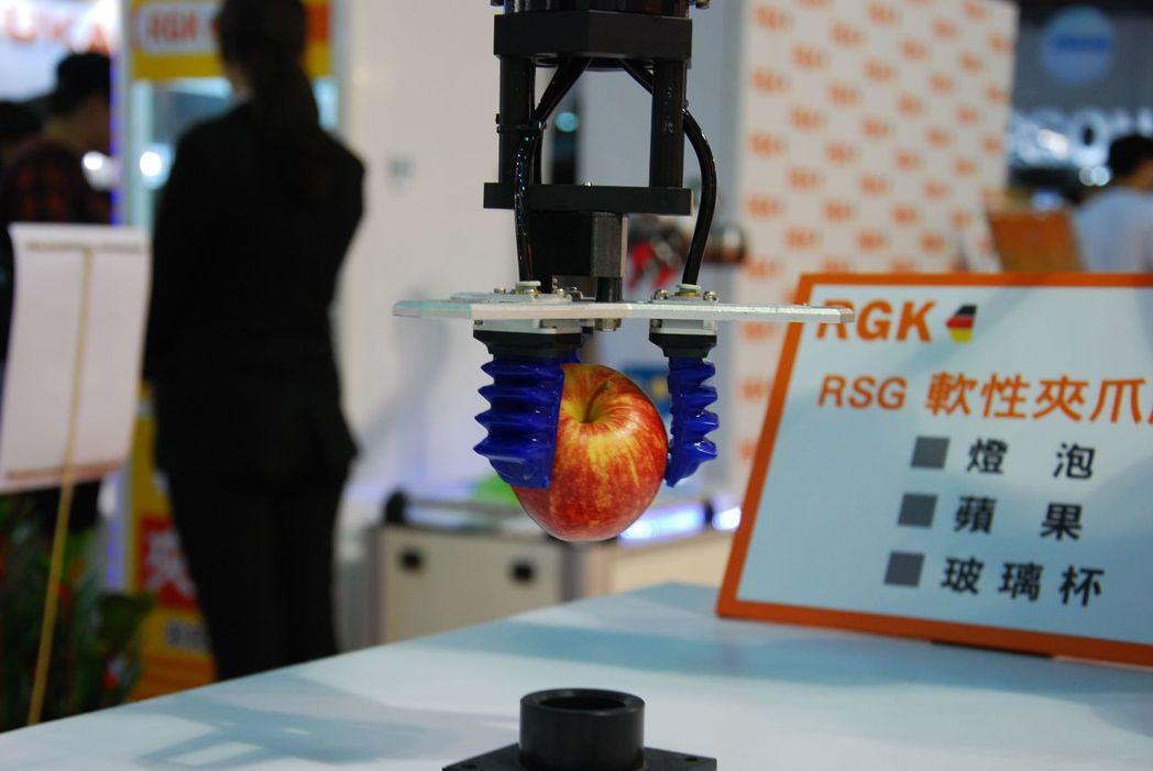 展覽現場軟性夾爪秀輕鬆夾蘋果。 楊鎮州/攝影