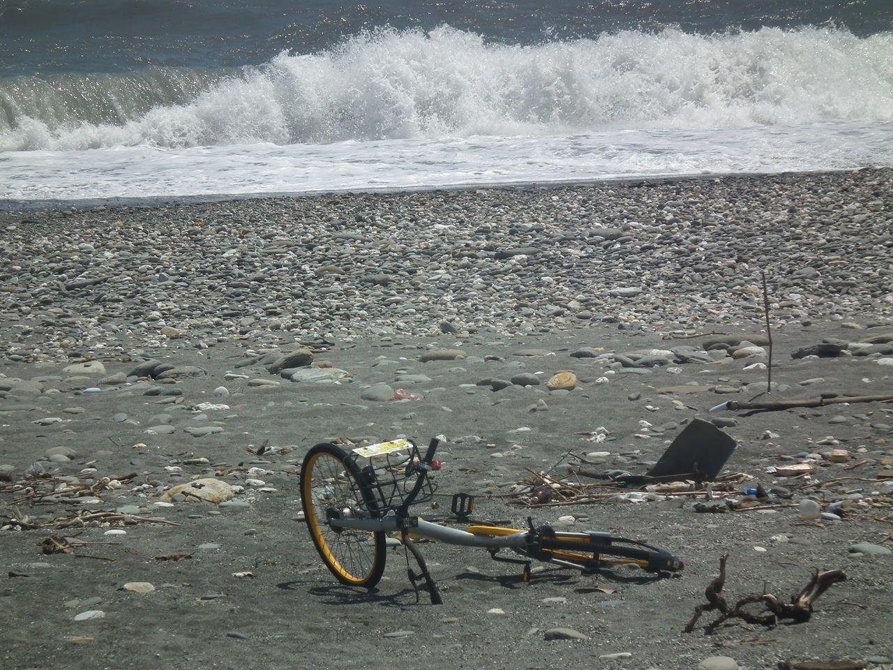 oBike單車被丟棄沙灘上,遊客開玩笑說:「中元普渡,當太平洋祭品了」。記者尤聰...