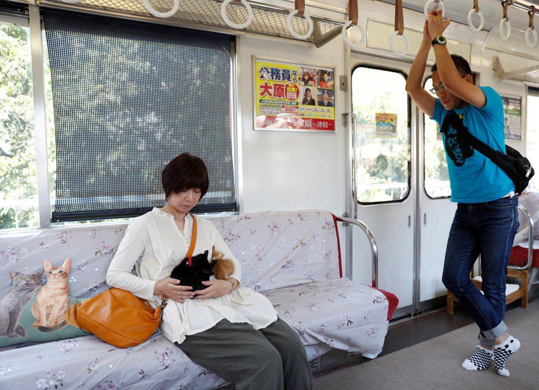 一名女乘客抱著兩隻貓。路透