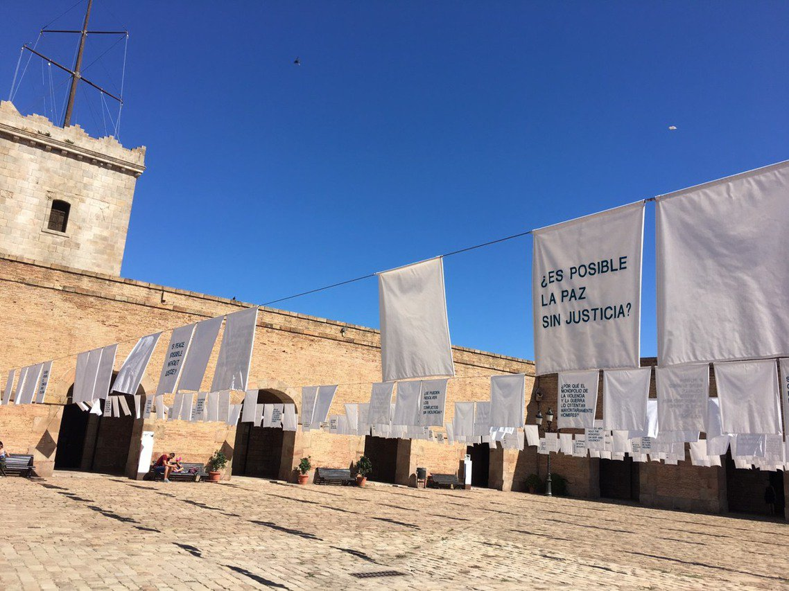 在要塞中庭,數百面白色麻布,上頭各自用英文、加泰隆尼亞文、西班牙文,刺上了不同的...