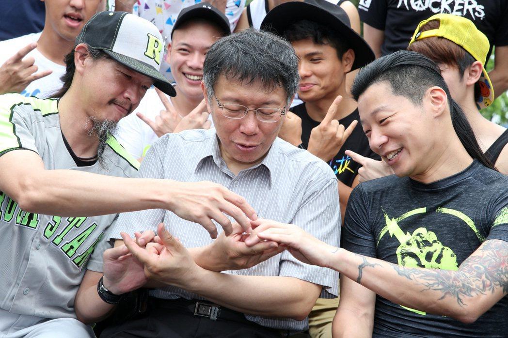 立委林昶佐(右)秀出手臂刺青,指導台北市長柯文哲(中)搖滾精神手勢。 本報資料照...