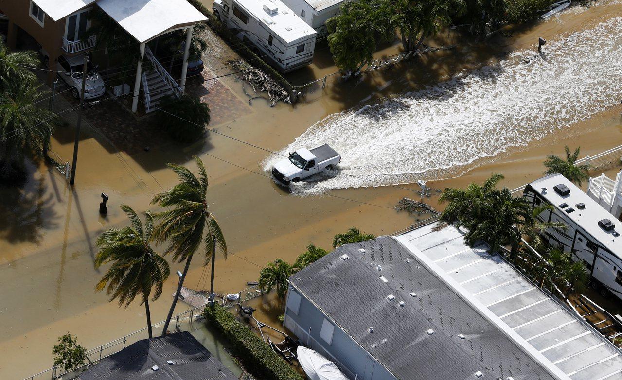 急救车行驶在南佛州Key Largo地区因飓风豪雨带来的洪水中,航空母舰已待命驰...