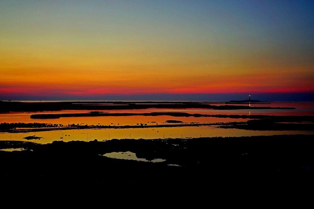 夜色初臨,目斗嶼燈塔一閃一閃的強光,呼應著夕陽西下後的一片金黃。 圖/作者自攝