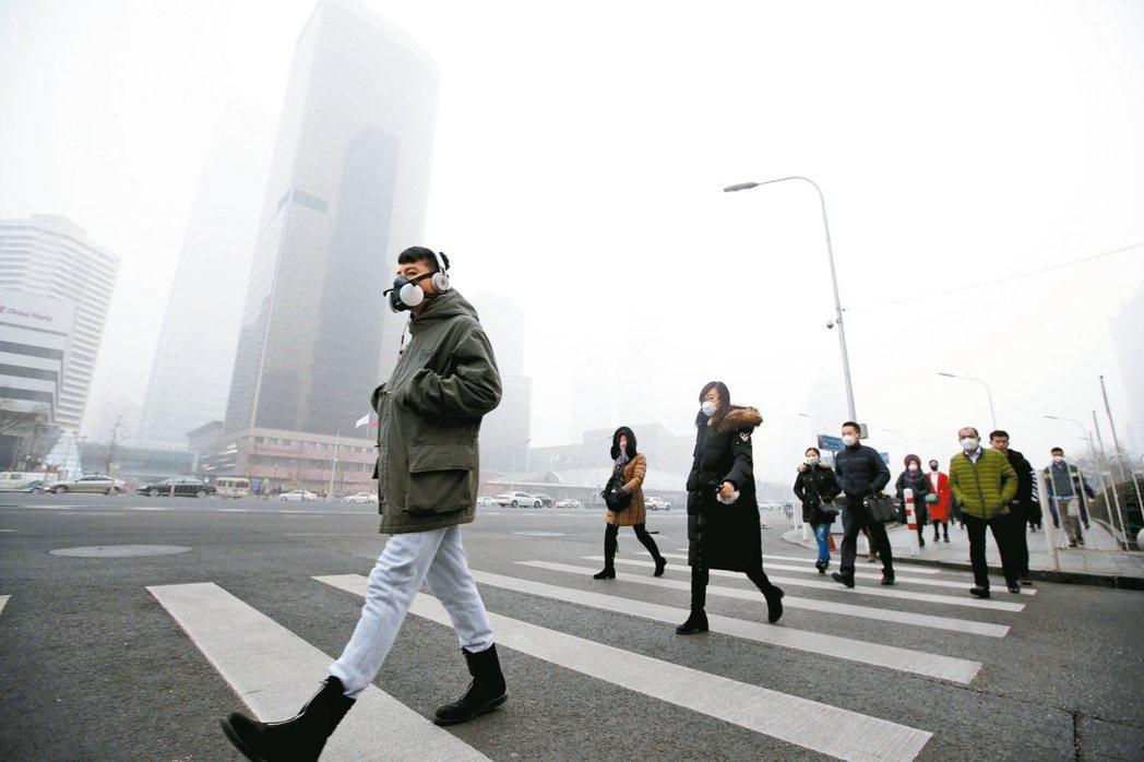 中國北京霧霾籠罩,民眾戴口罩保護呼吸道。 路透