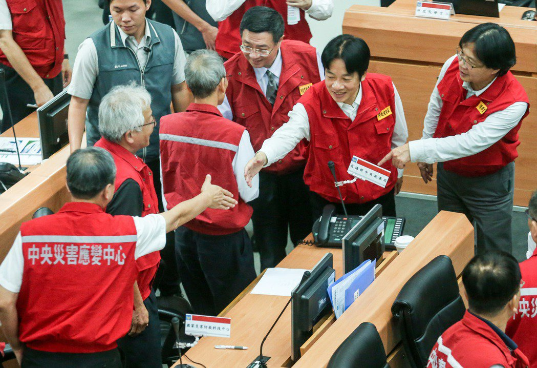 賴清德(右二)在葉俊榮(右一)陪同下向各部會前往災害應變中心的人員致意。記者鄭清...