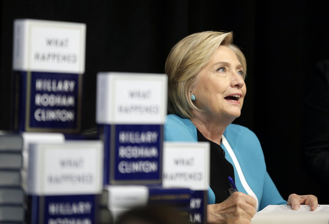 希拉蕊‧柯林頓12日在紐約聯合廣場龐諾書店舉辦的簽書會上,為粉絲購買的新書簽名。...