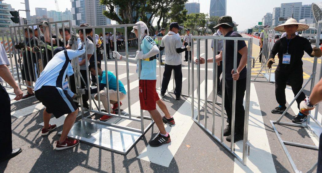 為了兼顧交通管制與民眾通行,警方在現場搬運拒馬管制道路。記者劉學聖/攝影